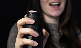 Девушка с газом, перцовый аэрозоль, конец-вверх, черная предпосылка, защита стоковые фото