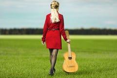 Девушка с гитарой в красном платье идя на зеленое поле стоковое изображение