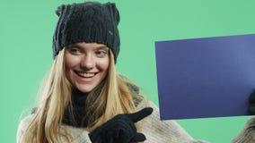 Девушка с голубым знаком на зеленой предпосылке видеоматериал