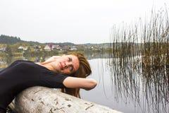 Девушка с диаграммой спорт сексуальной на предпосылке спокойного реки осени Йога, раздумье, ослабляет Стоковое фото RF