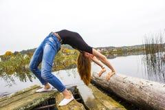 Девушка с диаграммой спорт сексуальной на предпосылке спокойного реки осени Йога, раздумье, ослабляет Стоковые Фотографии RF