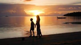 Девушка с детьми идет на прогулки и игру на пляже во время захода солнца видеоматериал