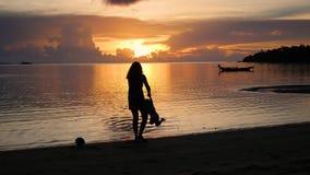 Девушка с детьми идет на прогулки и игру на пляже во время захода солнца акции видеоматериалы