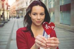 Девушка с леденцом на палочке в форме сердца Стоковые Изображения