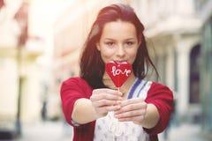 Девушка с леденцом на палочке в форме сердца Стоковая Фотография