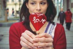 Девушка с леденцом на палочке в форме сердца Стоковые Фотографии RF