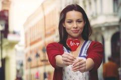 Девушка с леденцом на палочке в форме сердца Стоковые Фото