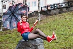Девушка с зонтиком читает книгу в парке стоковые фотографии rf