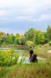Девушка с длинными темными волосами сидит на речном береге с ей назад и смотрит в расстояние Стоковые Изображения