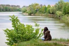 Девушка с длинными темными волосами сидит на речном береге с ей назад и смотрит в расстояние Стоковые Изображения RF