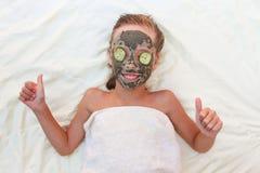 Девушка с лицевой маской глины и огурца Стоковая Фотография RF