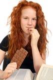 Девушка с книгами ест шоколад Стоковые Фотографии RF