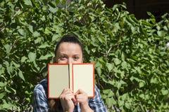 Девушка с книгой на предпосылке растительности, глаз Стоковая Фотография