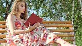Девушка с книгой на стенде в парке акции видеоматериалы