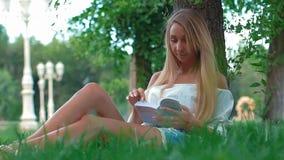 Девушка с книгой сидит на зеленой траве сток-видео