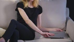 Девушка с компьтер-книжкой на софе Черная предпосылка видеоматериал