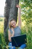 Девушка с компьтер-книжкой счастлива с успехом в ее деле стоковые изображения