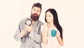 Девушка с кофейной чашкой, человек держит часы в руке Идеальная концепция утра Пары, семья проспали вверх в срок E стоковое изображение rf
