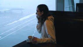Девушка с кофе говорит по телефону в гостиной аэропорта акции видеоматериалы
