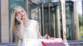 Девушка с красивыми пестроткаными пакетами после того как ходящ по магазинам вызывает ее друга и будет говорить о скидках и прода акции видеоматериалы