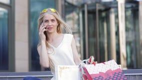 Девушка с красивыми пестроткаными пакетами после того как ходящ по магазинам вызывает ее друга и будет говорить о скидках и прода видеоматериал