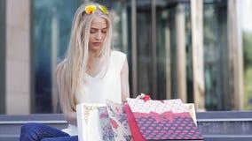Девушка с красивыми пестроткаными пакетами после того как ходящ по магазинам вызывает ее друга и будет говорить о скидках и прода сток-видео