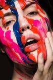 Девушка с краской на ее стороне Стоковые Изображения RF