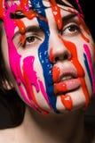 Девушка с краской на ее стороне Стоковая Фотография