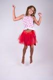 Девушка с красный скакать юбки счастливый с руками вверх Стоковое Изображение RF
