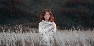 Девушка с красными волосами в оболочке в сером связанном свитере в поле стоковое фото