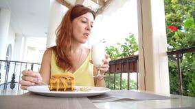 Девушка с красными волосами ест десерт в ресторане акции видеоматериалы
