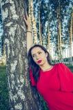 Девушка с красными губами в красном стиле моды платья стоит в роще березы стоковые изображения rf