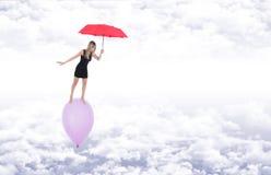Девушка с красным зонтиком идя barefoot на летание воздушного шара внутри Стоковое Изображение RF