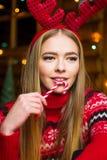Девушка с красным леденцом на палочке в праздничной украшенной окружающей среде Стоковые Фото