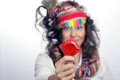 Девушка с красным пакетом презерватива в руке Стоковые Изображения