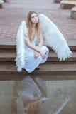 Девушка с крылами около воды Стоковое Фото