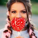 Девушка с леденцом на палочке Женщина модели очарования красоты с конфетой леденца на палочке ультрамодного пинка удерживания вол стоковое фото