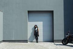 Девушка с малой сумкой около здания и мотоцилк Стоковые Изображения RF