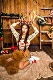 Девушка с медведем в ее руке сидя в комнате с деревянными стенами Стоковые Изображения RF