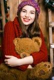 Девушка с медведем в ее руке сидя в комнате с деревянными стенами Стоковое Фото