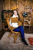 Девушка с медведем в ее руке сидя в комнате с деревянными стенами Стоковое фото RF