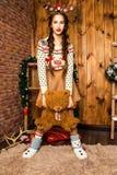 Девушка с медведем в ее руке стоя в комнате с деревянным wa Стоковое фото RF