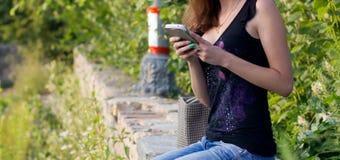 Девушка с мобильным телефоном сидит на обочине Стоковое Фото