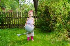 Девушка с моча чонсервной банкой в саде Стоковое Изображение RF