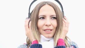 Девушка с наушниками слушая к музыке и подмигивать видеоматериал