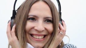 Девушка с наушниками слушая к музыке и подмигивать сток-видео