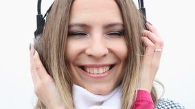 Девушка с наушниками слушая к музыке и дуя поцелуй акции видеоматериалы