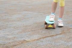 девушка с одной ногой стоит на том основании и другое с ногой на скейтборде против предпосылки асфальта стоковая фотография rf