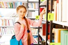 Девушка с оплеткой стоит близко книжные полки в библиотеке Стоковые Изображения RF