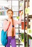 Девушка с оплеткой стоит близко книжные полки Стоковое Изображение RF